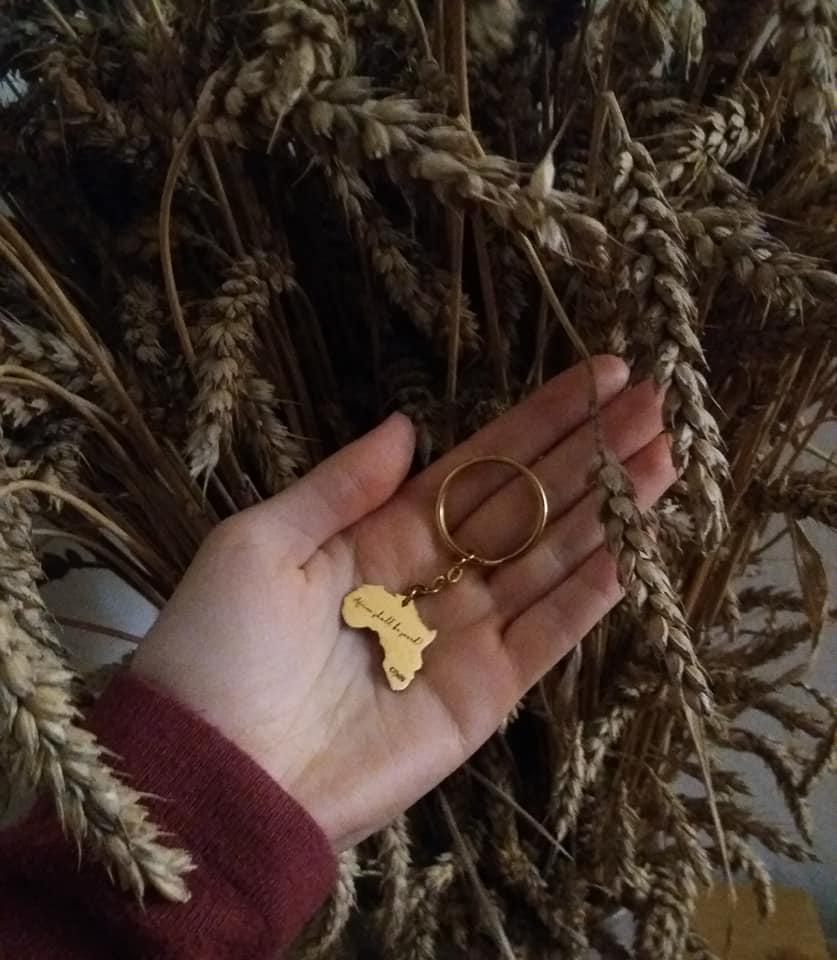 Schüsselanhänger in Gold mit der Aufschrift - Africa shall be saved! CfaN - auf Hand vor Kornähren
